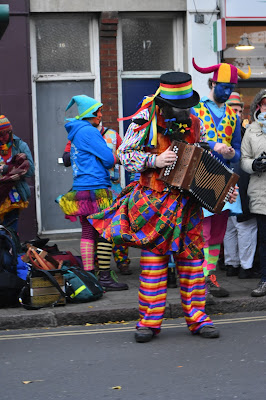 a colourful man playing the accordion