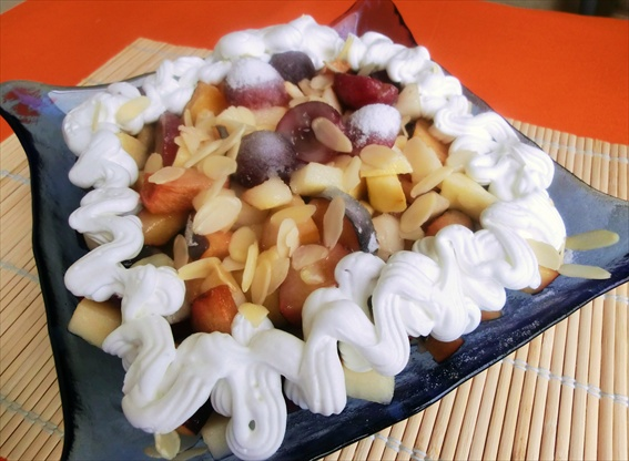 insalata (dessert) di frutta con panna e vino (mele, pere, prugne e uva)