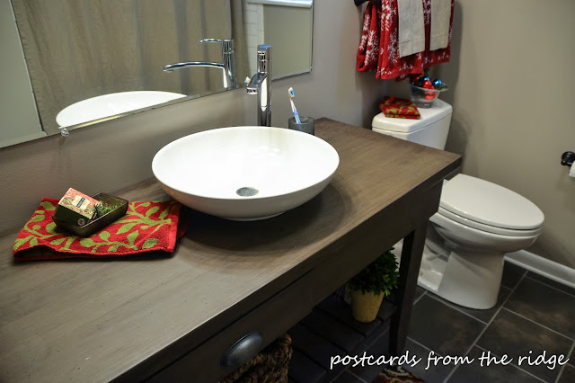 Open shelf vanity, dark bathroom floor tile, Benjamin Moore Plymouth Rock paint