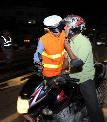 SEORANG anggota polis menghidu bau nafas seorang penunggang motosikal semasa satu sekatan jalan raya diadakan di Kathmandu pada 17 Julai lalu.