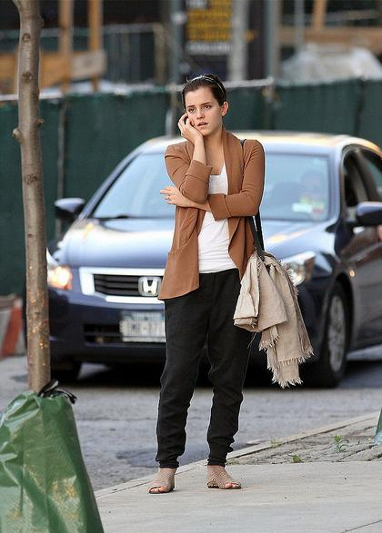 emma watson standing on street and talking in her phone