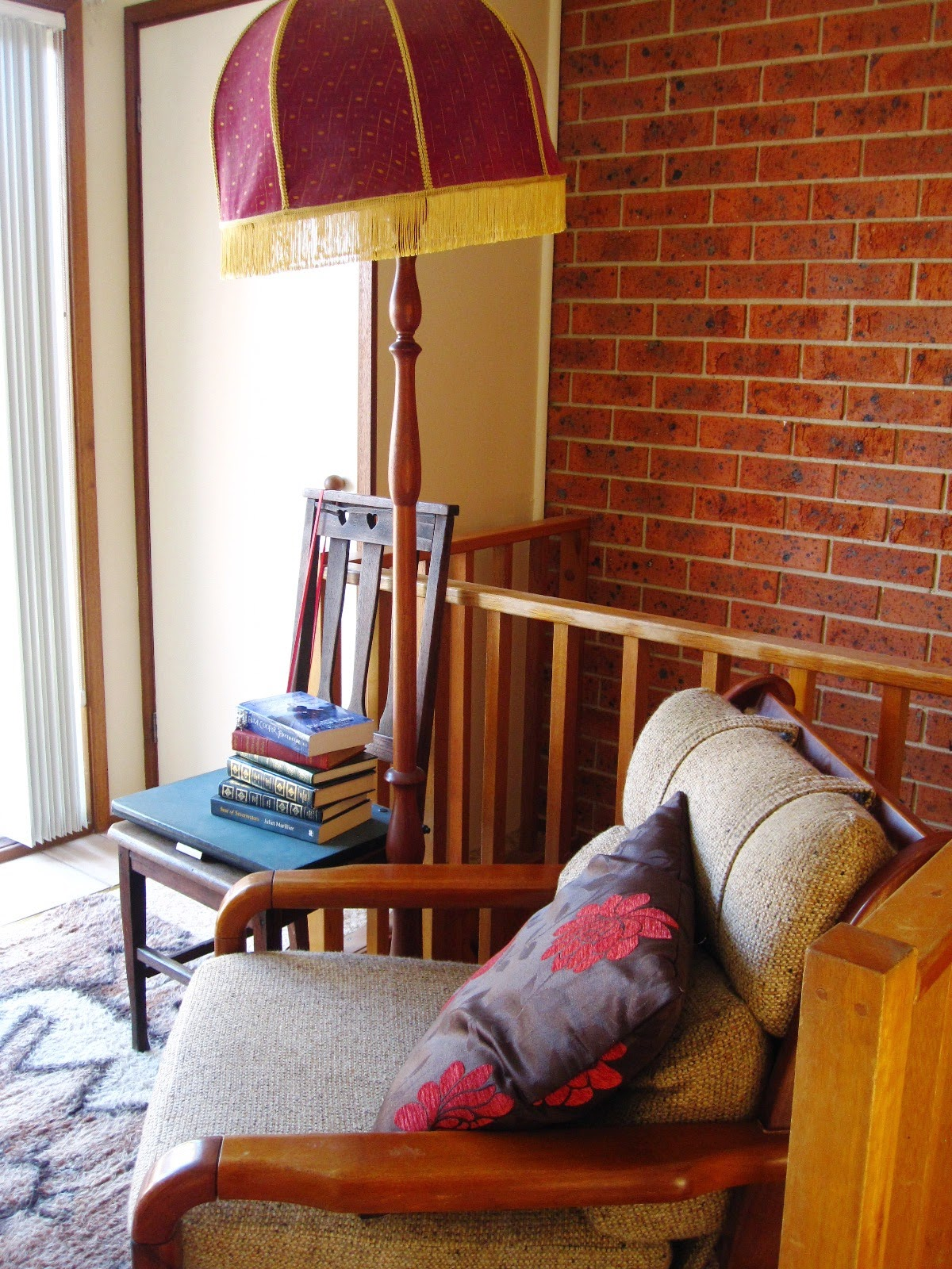 A reading nook which includes a 1970s comfy chair and floor rug, a vintage wooden floor lamp and a side chair holding a pile of books.