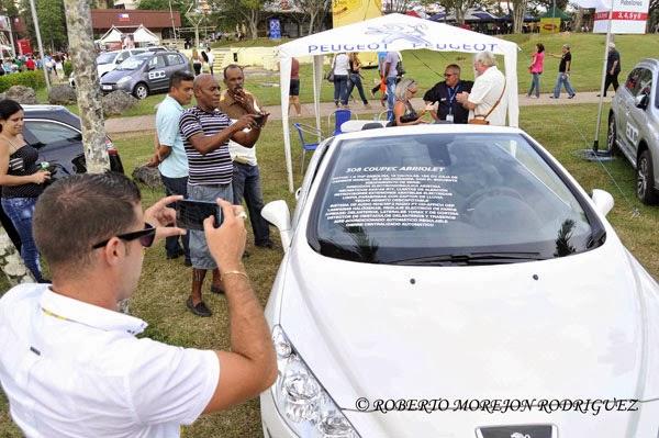 Personas toman fotografías a un vehículo de la marca Peugeot, expuesto en el Pabellón de Francia durante la XXXI Feria Internacional de La Habana, FIHAV 2013