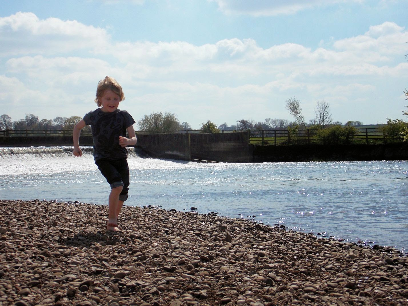 boy running at stony beach