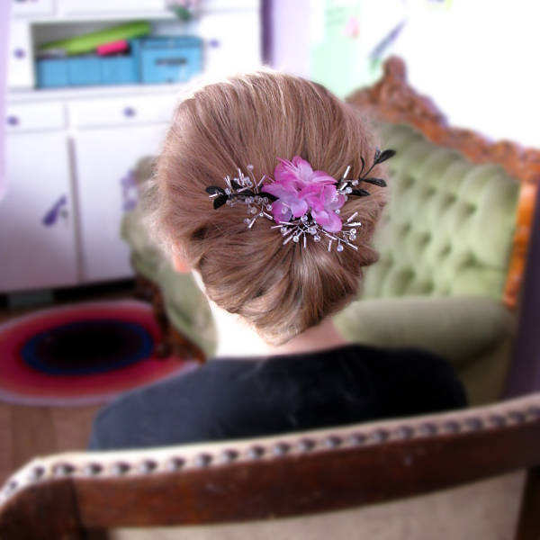 Elegancki, niski kok ślubny ozdobiony kwiatami