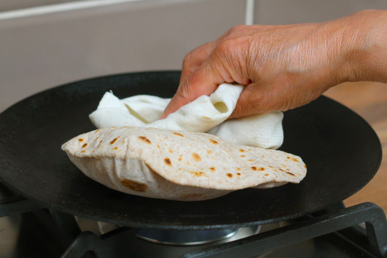 Encouraging the roti to puff up