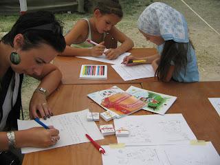 Napszemüveges, rövid sötét hajú édesanya véleményt ír egy sima lapra a tevékenységről. Háttérben két nagyobb lányka elmélyülten olvassák a feladatlapot.
