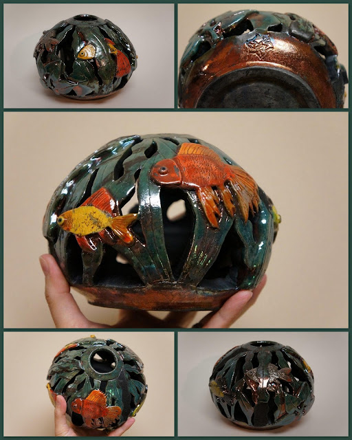Unique and beautiful raku pottery vessel with carved fish bowl design.