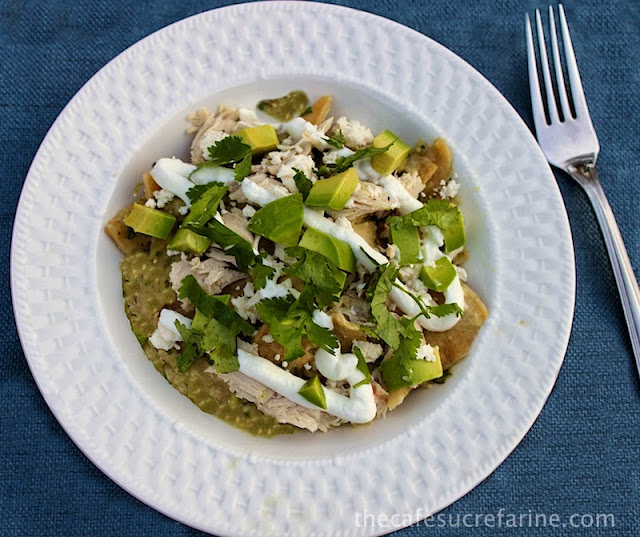 An overhead photo of a white plate of Chicken Chilaquiles Verde on a blue placemat.