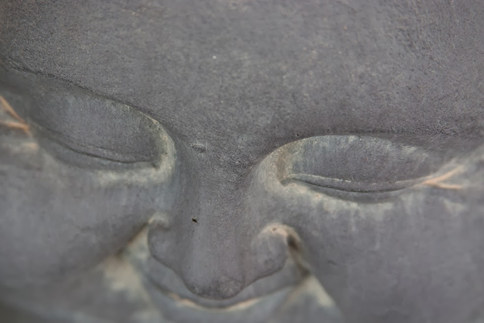 smiling face of a fat grey buddha