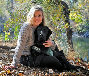Emily sits with her black Lab guide dog puppy on the ground surrounded by leaves