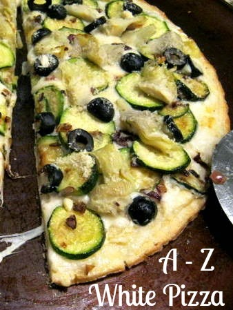 Homemade pizza with goodness from A to Z: Alfredo sauce, artichokes, and zucchini. Delicious!