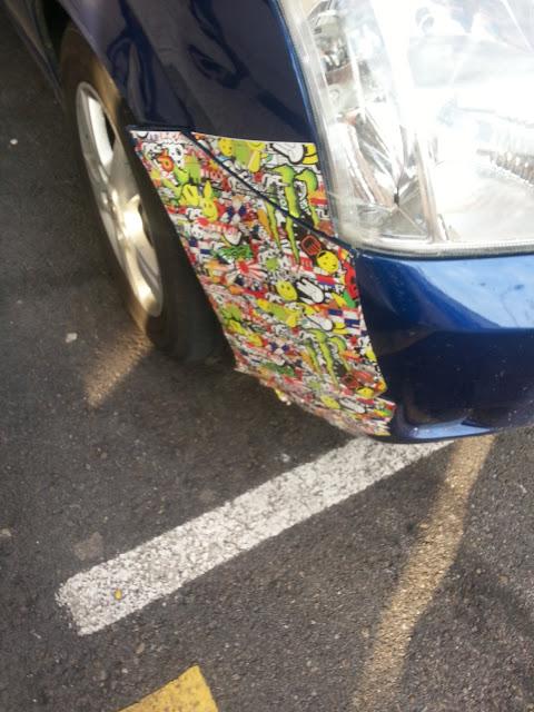 Fotografía de la parte delantera del un vehículo al que le han puesto un parche de papel, como si quisieran tapar arañazos en la chapa o algo similar.  Lo mejor es que el papel es gracioso porque tiene mucho colorido y dibujos de caras sonrientes y otras cosas
