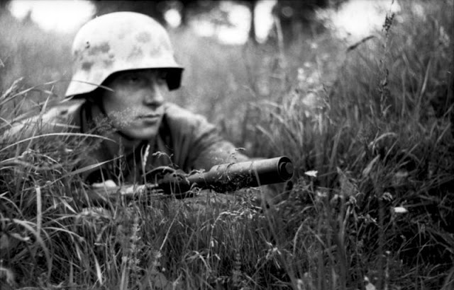 A concealed German soldier in northern France, 1944. His Karabiner 98k is equipped with a Gewehrgranatgerät cup-type grenade launcher attachment.