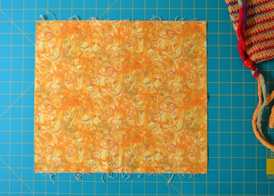 The fabric cut to height and width is laid out flat on the cutting mat. The side edges of the fabric are straight and parallel.  The grid indicates the dimensions of the fabric.  Part of the crochted bag can be seen in the top corner for a sense of scale.