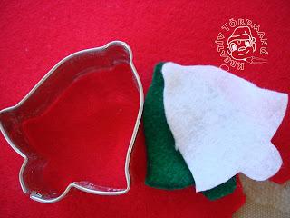 Szöveg: A mézeskalács figura segítségével kivágod a filcből a formát. Kép: Piros filcen csengő formájó mézeskalácskivágó, mellette zöld és fehér már kivágott csengőformájú filcdarabkák.