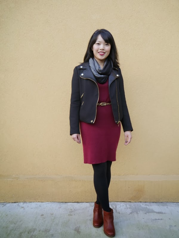 Vancouver blogger Lisa Wong of Solo Lisa wears a black moto jacket, black/grey colourblocked jersey scarf, burgundy sweater dress, leopard print belt, black tights, and cognac leather booties.