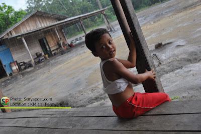 Suasana anak kecil menunggu hujan reda