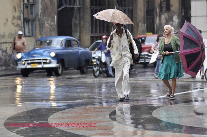 Personas caminando bajo la lluvia en el Paseo del Prado en La Habana, Cuba, el 15 de febrero de 2013.