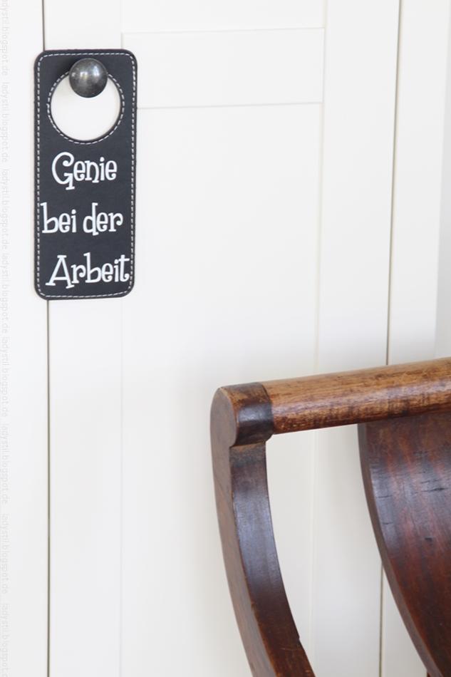 """Türschild """"Genie bei der Arbeit"""" hängt an weißem Schrank"""