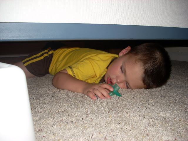Child sleeping under his bed