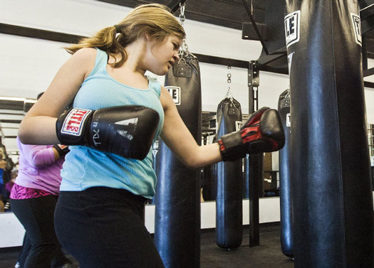 Girl hitting punching bag