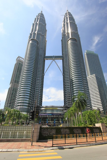 The full view of Petronas Twin Towers from the busy main street in Kuala Lumpur, Malaysia