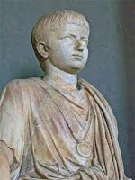 Estatua de un niño portando la bulla que lo identifica como menor