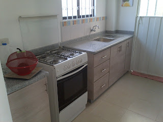 image of the kitchen plac for cooker comrising sink work tops cupboards and over head cupboards
