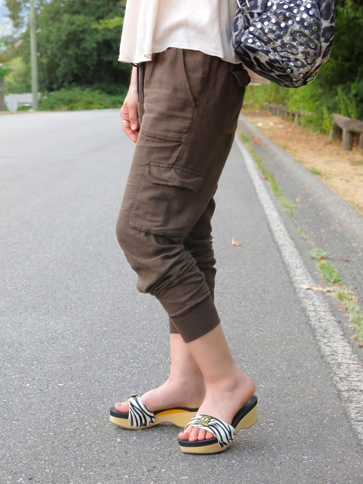 styling slouchy cargo pants with a Zara top, zebra-striped slides, and a leopard backpack