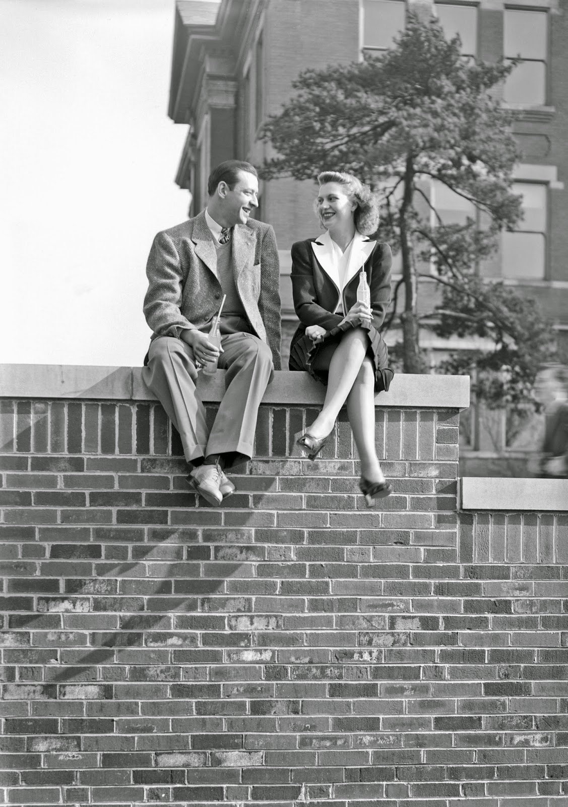 Man and woman sitting on brick wall drinking soda, 1939