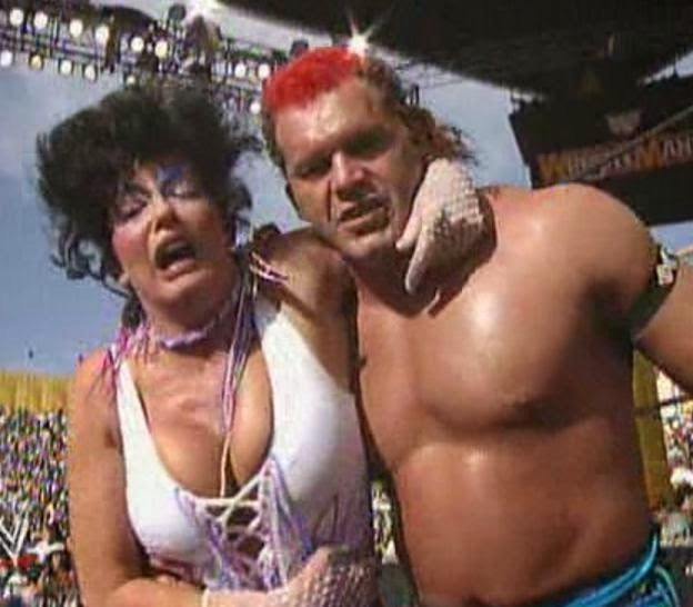 WWE / WWF WRESTLEMANIA 9: Tatanka helps Sensational Sherri to the back following his count-out win over Intercontinental Champion, Shawn Michaels