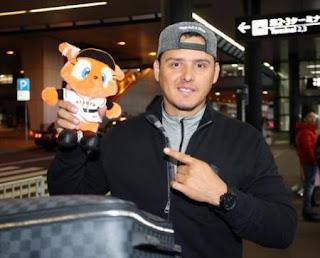 <巨人外国人選手来日>マスコット人形を手に笑顔のクルーズ