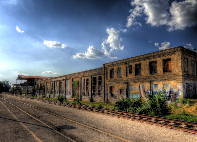 Abandoned railway warehouse across tracks facing NW