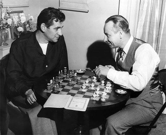 Le grand chef d'orchestre et compositeur Leonard Bernstein et le violoniste de talent Zino Francescatti souriant devant une partie d'échecs au Carnegie Hall