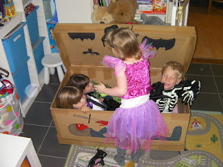 4 children trying to get into the same halloween coffin