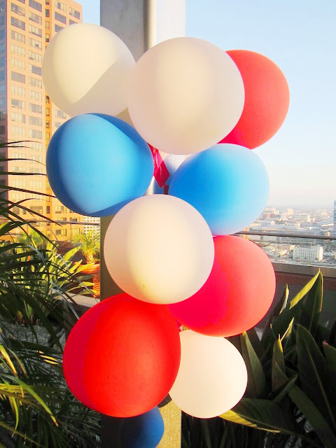 Red, white and blue balloons tied to a pole with plants and a view of a city in the background