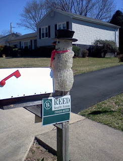 snowman on a mailbox during the spring