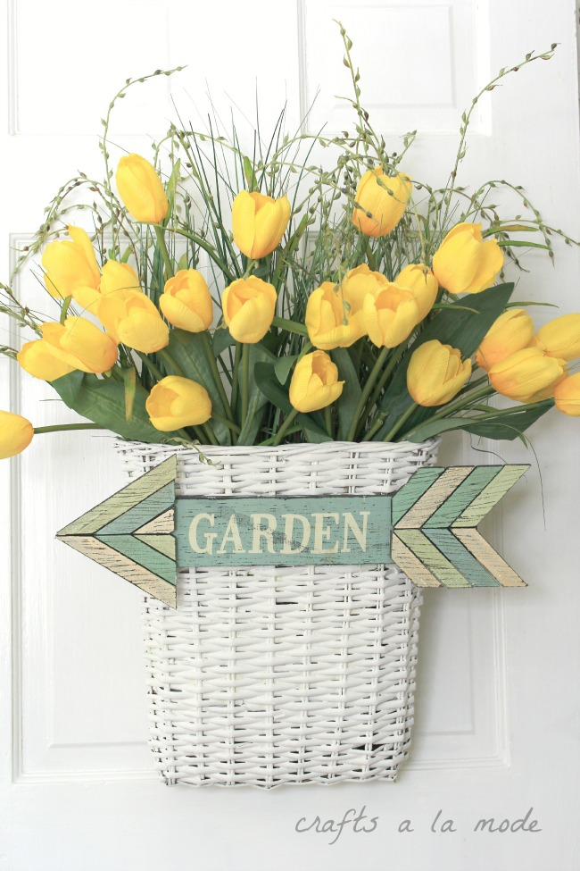 Yellow tulips in a white basket  for front door decor.