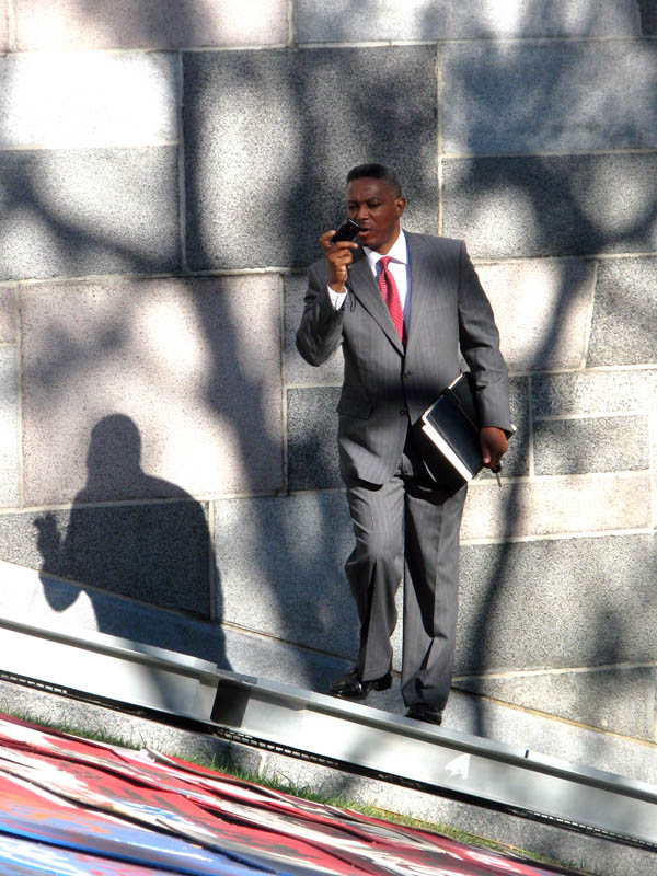 Occupy Los Angeles - man in a gray suit holding a briefcase taking pictures