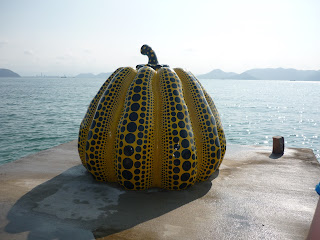 Famous Naoshima pumkin. It is about as tall as a person, yellow with black spots and is located in a platform that juts out a little into the ocean