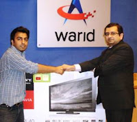 Mr. Airaj Asadullah of Hyderabad, winner of the first &#8220;Warid Reverse Auction&#8221; receiving the 40&#8221; LCD TV with the winning bid of Rs 38