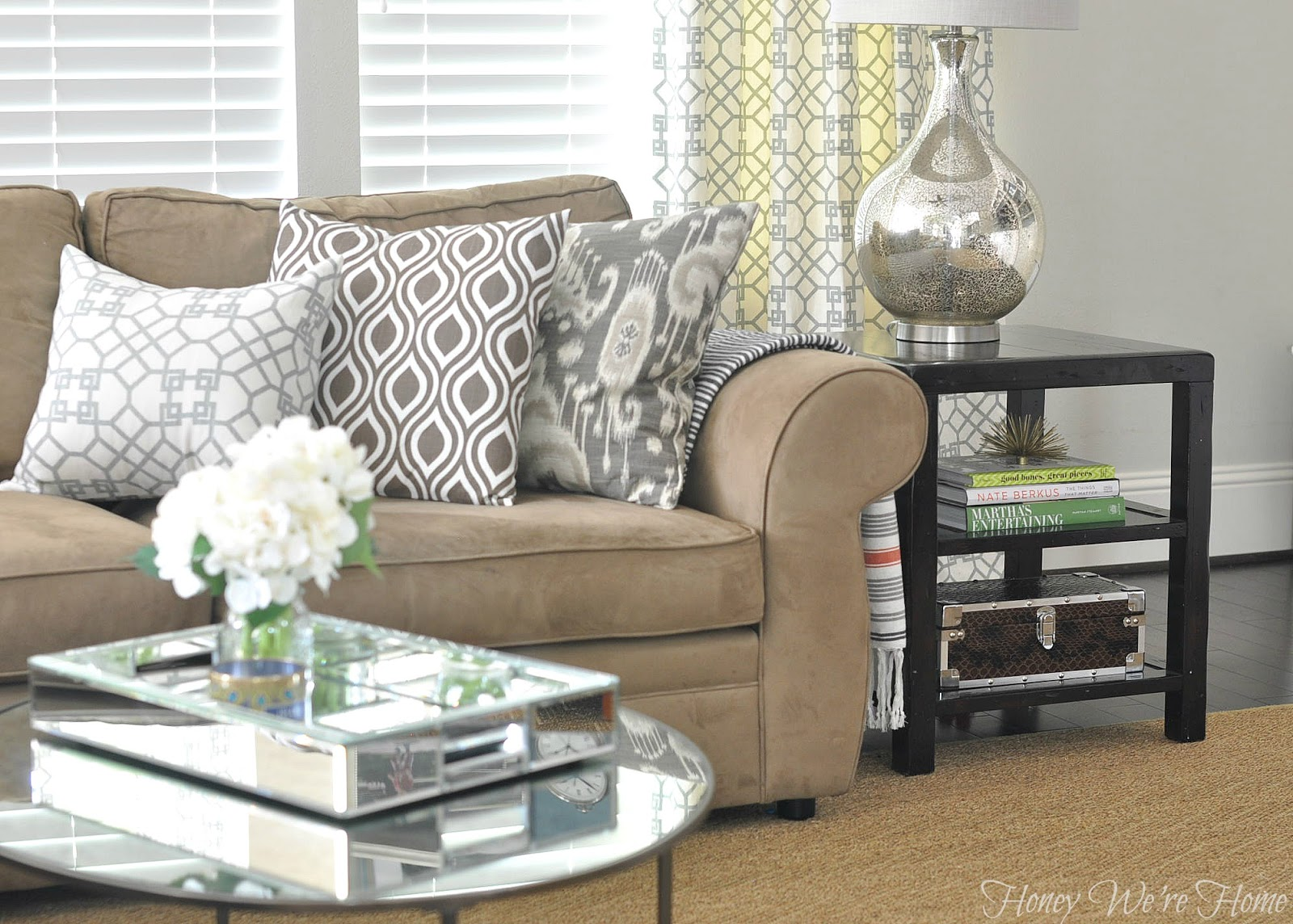 Transitional living room features a white pit sectional accented with yellow pillows, brown pillows as well as blue and yellow suzani pillows surrounded by windows and .