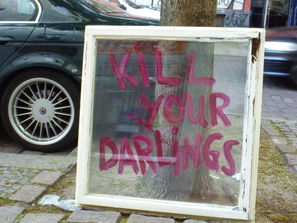 """""""Kill your darlings"""" steht in roten Lettern auf einem alten Fenster, das an einen Baum gelehnt wurde."""