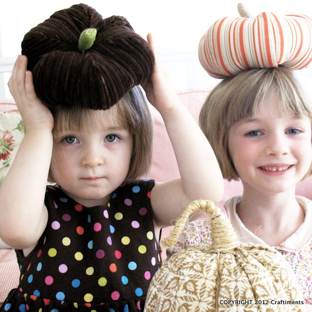 Kids balancing fabric pumpkins on their heads