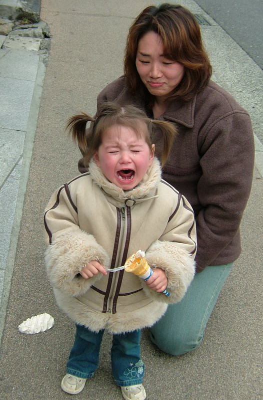 A young Japanese girl cries after dropping her ice-cream