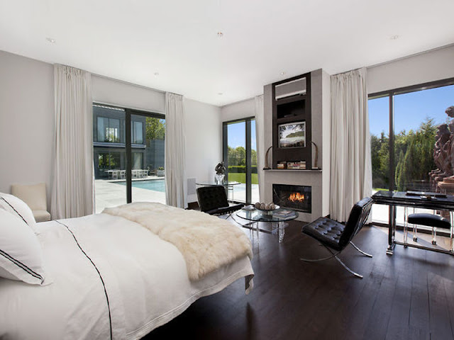Bedroom with white bed, surrounded by large windows with floor length white curtains overlooking the backyard with a pool