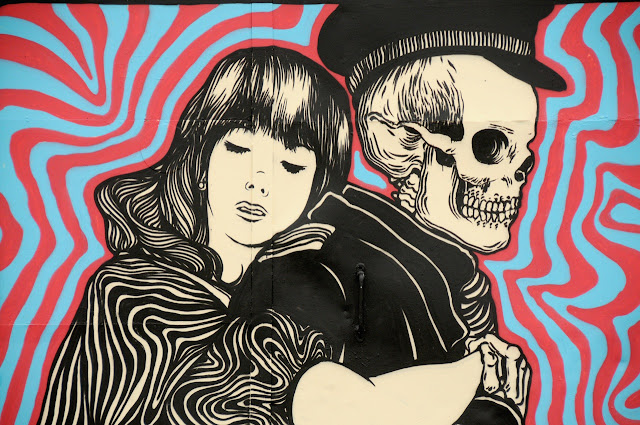 details of street art piece by broken fingaz in amsterdam - skeleton with girl