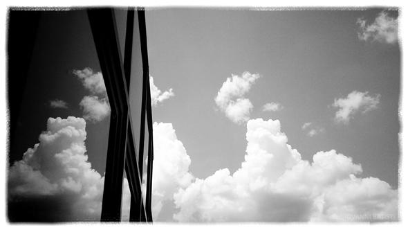 Fotografia in bianco e nero di nuvole riflesse nei vetri di un edificio