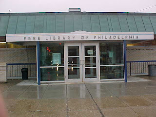 The front of a single story library with a green roof and two glass doors. Foreground is sidewalk sheeted in rain.